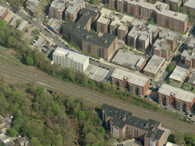 65-70 Austin Street (low-rise building abutting the train tracks, center), image from Bing Maps